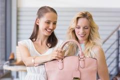 Two happy women looking at handbag Stock Image
