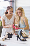 Two happy women looking at heel shoe Royalty Free Stock Images