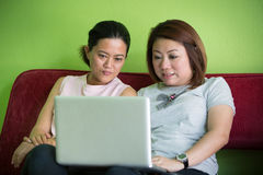 Two Happy Women Looking At Laptop While Lying Stock Image