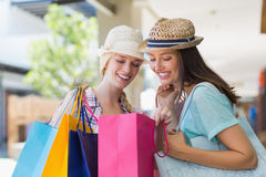 Two happy women looking at shopping bags Stock Photos