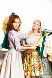Two happy women measure size of the skirt in shop Royalty Free Stock Photo