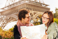 Two happy women with a paper tourist map in Paris Stock Photo