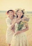 Two happy women. Portrait of two happy women with flowers in summer field stock photo