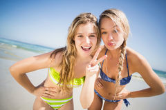 Two happy women pouting and gesturing on the beach Royalty Free Stock Image