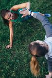 Two happy women practicing yoga on grass standing in side plank posture, Vasisthasana, touching hands Royalty Free Stock Image