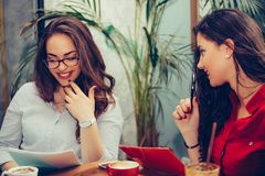 Two happy women reading documents together while sitting in the table in cafe royalty free stock images