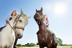 Two happy women riding beautiful purebred horses. Close-up portrait of two happy women riding beautiful purebred horses outdoor stock photo