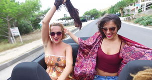 Two happy women riding in cabriolet and playing with their scarves in the wind stock footage