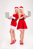 Two happy women in santa cloth using laptop computer Royalty Free Stock Photography
