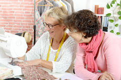 Two happy women sewing in their workshop Royalty Free Stock Image