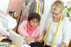 Two happy women sewing together Royalty Free Stock Photos