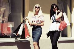 Two happy women with shopping bags against a mall  Stock Photo