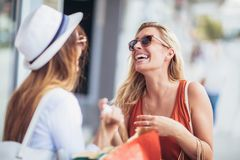 Two happy women with shopping bags enjoying in shopping. Having fun in the city royalty free stock photography