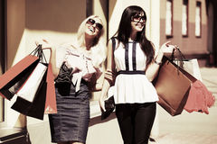 Two happy fashion women with shopping bags walking in city street. Two young fashion women with shopping bags walking in a city street