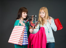 Two happy women shopping in clothes store. Royalty Free Stock Image