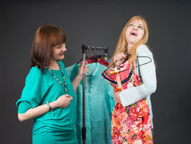 Two happy women shopping in clothes store. Royalty Free Stock Photos