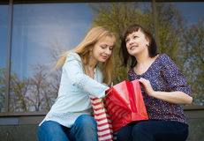 Two happy women shopping in clothes store. Royalty Free Stock Images
