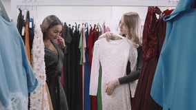 Two happy women shopping in clothes store, choose dress. Blonde and arabian young girl. stock video footage