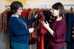 Two happy women shopping in clothes store Royalty Free Stock Photos