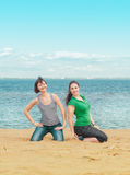 Two happy women sitting on the beach Royalty Free Stock Photos