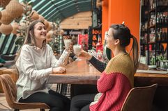 Two happy women are sitting in a cafe, drinking milkshakes. Telling each other funny stories, being in a good mood, laughing happily. Best friends have fun stock images