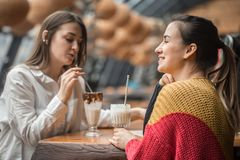Two happy women are sitting in a cafe, drinking milkshakes. Telling each other funny stories, being in a good mood, laughing happily. Best friends have fun stock photos