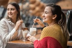 Two happy women are sitting in a cafe, drinking milkshakes. Telling each other funny stories, being in a good mood, laughing happily. Best friends have fun royalty free stock images