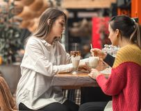 Two happy women are sitting in a cafe, drinking milkshakes. Telling each other funny stories, being in a good mood, laughing happily. Best friends have fun royalty free stock image