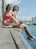 Two happy women sitting near the bridge on the sea Royalty Free Stock Photos