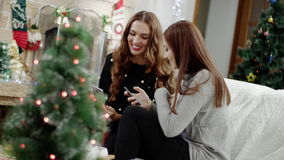 Two happy women with smartphone at christmas party. Two happy women with smartphone in christmas party. Ladies looking in phone stock video