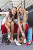 Two happy women smiling at camera and trying on shoes Royalty Free Stock Photos