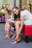 Two happy women smiling at camera and trying on shoes Stock Image