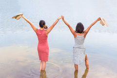 Two happy women standing in water. Two happy friends standing together in water of lake Stock Photography