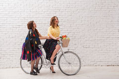 Two happy women in summer dresses are riding together on a retro bike. Two happy women in summer dresses are riding together on a retro bike Stock Photos