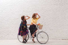Two happy women in summer dresses are riding together on a retro bike. Two happy women in summer dresses are riding together on a retro bike Royalty Free Stock Photos