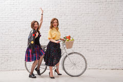 Two happy women in summer dresses are riding together on a retro bike and gesture hands forward.  Stock Image