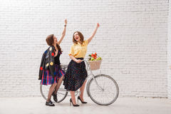 Two happy women in summer dresses are riding together on a retro bike and gesture hands forward.  Stock Images