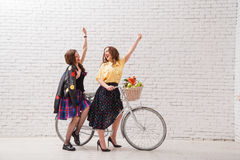 Two happy women in summer dresses are riding together on a retro bike and gesture hands forward. Two happy women in summer dresses are riding together on a Stock Photography