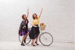 Two happy women in summer dresses are riding together on a retro bike and gesture hands forward. Two happy women in summer dresses are riding together on a Royalty Free Stock Image