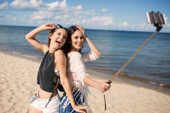 Two happy women taking selfie on beach fooling around Royalty Free Stock Images
