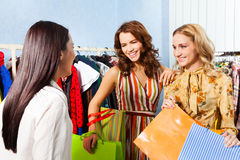 Two happy women talking with shop assistant Stock Images