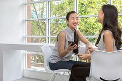 Two happy women using Mobile Phone and tablet sitting in coffee shop. Two young women best friends smiling using a tablet. Female stock images