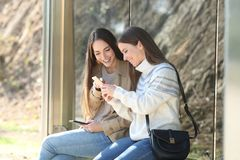 Free Two Happy Women Waiting In A Bus Stop Checking Phones Stock Photo - 165764790