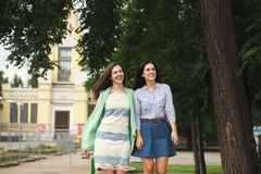 Two women walking in the summer park royalty free stock photos