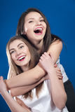 Two happy young beautiful woman friends. Two happy young beautiful women friends on each other laughing with mouth wide open on blue background Royalty Free Stock Image