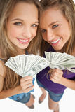 Two happy young beauty holding dollars Stock Photography