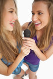 Two happy young beauty singing together Stock Photos