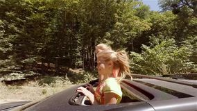 Two happy young blondes laughing leaping out of hatch of the car on the move against the forest. HD stock footage