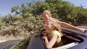 Two happy young blondes laughing leaping out of hatch of the car on the move against the forest. HD stock video