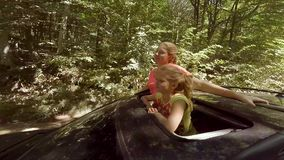 Two happy young blondes laughing leaping out of hatch of the car on the move against the forest. HD stock video footage